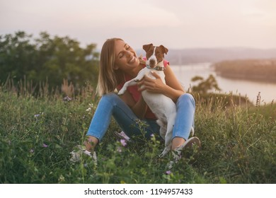 Beautiful woman enjoys spending time with her dog Jack Russell Terrier outdoor with a cityscape and river view behind her.Image is intentionally toned.