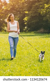 Beautiful woman enjoys walking with her  cute dog Jack Russell Terrier in the nature.Image is intentionally toned.