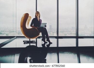 Beautiful woman entrepreneur is sitting alone with laptop on modern yellow curved armchair in office interior with reflections on high floor of skyscraper with copy space place for logo or your text