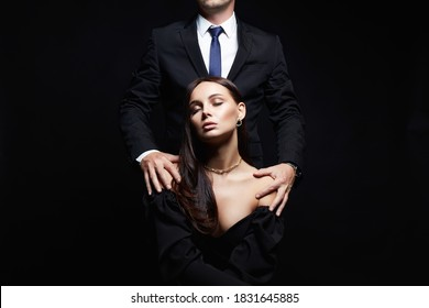 beautiful woman in evening dress in the hands of man in a suit. Couple over black background. Adorable, elegant girl seducing her handsome boyfriend