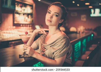 Beautiful woman in evening dress sitting near bar counter