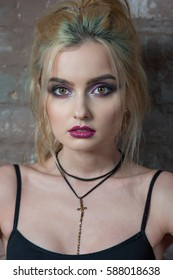 Beautiful woman with evening make-up. Beauty fashion photo. The girl with a bright make-up against the background of a brick wall. Beauty portrait
