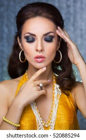 Beautiful woman with evening make-up and curly hair and yellow dress with jewelry pearls hand pointing to face make-up. Smoky eyes. Fashion portrait photo. Picture taken in the studio over bokeh shiny