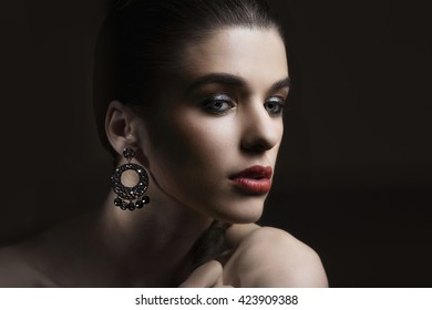 Beautiful woman with evening make-up. Jewelry and Beauty. Fashion photo.  Perfect make-up and hair. Sexy look in down. Close-up portrait.