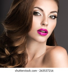 Beautiful woman with evening make-up, pink lips and curls. Beauty face. Picture taken in the studio on a gray background.