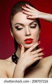 Beautiful woman with evening make-up and red nails with thorns. Picture taken in a studio on a red background.