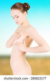 Beautiful woman examining her breast.