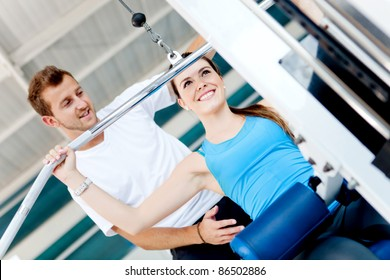 Beautiful woman exercising at the gym with her trainer