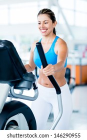 Beautiful woman exercising at the gym on an x-trainer