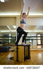 Beautiful woman exercising on wunda chair in gym