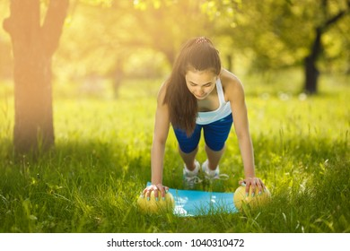 Beautiful woman exercising outdoors. Cheerful slim girl doing workout at the park in summer time. Woman doing slimming strap
