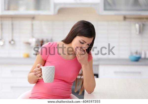 Bella donna vivendo segni di gravidanza in cucina