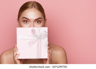 Beautiful woman with eye makeup and nude shoulders covering lower face with gift box. Copy space in right side. Isolated on rose background