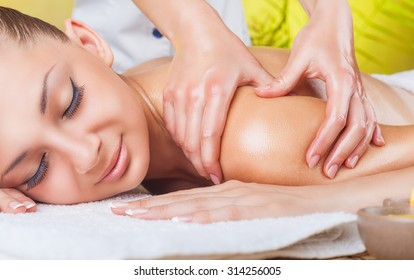 Beautiful woman with eyes closed receiving a massage at the spa salon