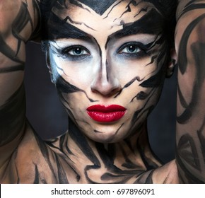 A beautiful woman with face art and red lips looks at us intently.