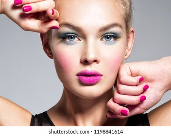 Beautiful woman face with blue makeup of eyes and pink nails. Glamour fashion model.  Fashion portrait of a attractive woman with bright makeup.  Gorgeous girl.