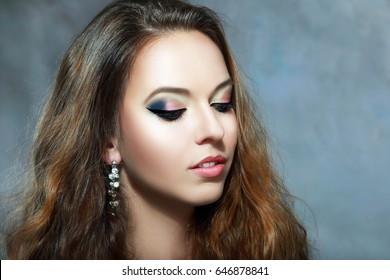 Beautiful woman face with bright make up eyes closed over dark background