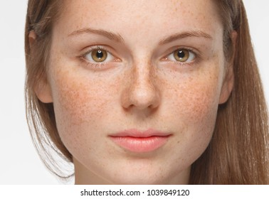 Beautiful woman face close up with freckles isolated, cleam skin
