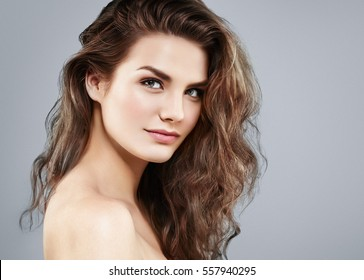 Beautiful woman face close up portrait young curly hair studio on gray