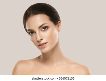 Beautiful woman face close up studio over beige