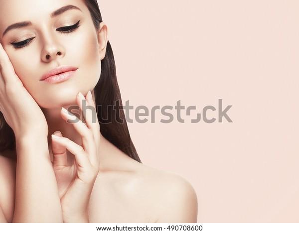 Beautiful woman face close up studio on pink