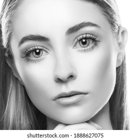 Beautiful woman face close up, healthy skin, nude make-up, eyes,  portrait in studio on white. Monochrome