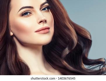 Beautiful woman face closeup with beauty makeup and brunette hair closeup