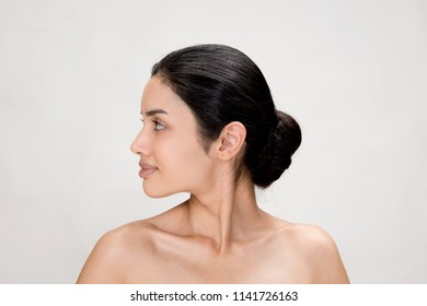 Beautiful Woman Face Closeup.Beauty Spa Woman with perfect Skin Portrait. Elegant Brunette Spa Facial Girl. Proposing a Product. Gestures for Advertisement Studio on Gray.Copy Space  for Text.