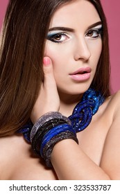 Beautiful woman face with colorful make-up and pink lips. Woman with jewelry.