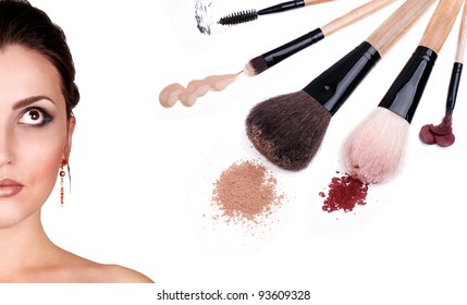 Beautiful woman face with cosmetics and makeup brushes
