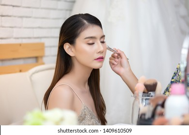 Beautiful woman face. Hand of make-up