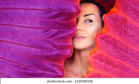 Beautiful Woman face with Natural  make-up on a tropical Ultra Violet leaf background in the jungle. Sexy beautiful woman behind the colorful leaves. Pure cosmetic and wellness art concept. Neon
