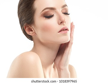 Beautiful woman face neck shoulders is touching her face. close up portrait young studio on white