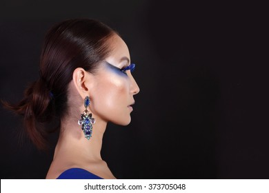 Beautiful woman face. Perfect makeup. Asian woman with make-up in blue. Portrait of the beautiful asian girl with creative art makeup with bright colors