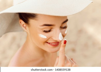 Beautiful Woman Face Portrait Beauty Skin Care Concept. Suncream. Suntan Lotion Beautiful Woman Applying on beautiful on Face. Sunscreen Solar Cream. Sun protection.The Girl Uses  Moisturizer Sunblock
