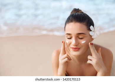 Beautiful Woman Face Portrait Beauty Skin Care Concept. Suncream. Suntan Lotion Beautiful Woman Applying on beautifu on Face. Sunscreen Solar Cream. Sun protection.The Girl Uses  Moisturizer Sunblock
