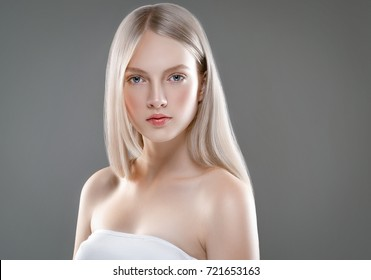 Beautiful Woman Face Portrait Beauty Skin Care Concept. Fashion Beauty Model with beautiful hair over gray background