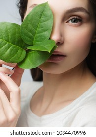 beautiful woman face portrait with green leaf , concept for skin care