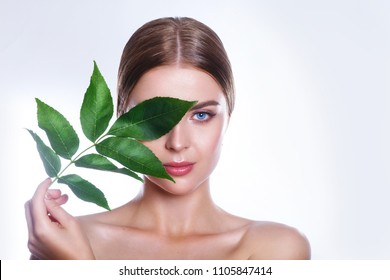 Beautiful woman face portrait with green leaf concept for skin care or organic cosmetics