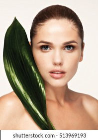 beautiful woman face portrait with green leaf , concept for skin care or organic cosmetics