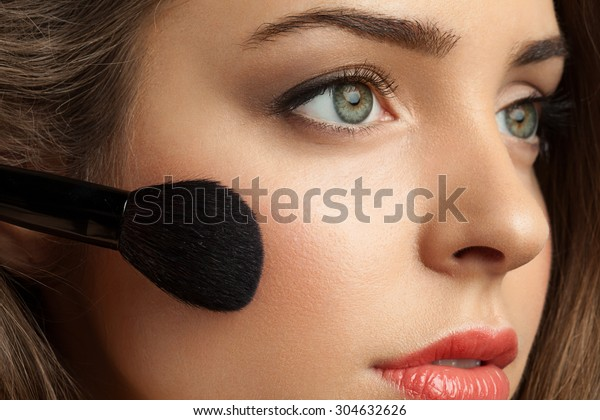 Beautiful woman face powders, and apply blush to the cheekbones