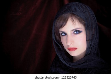 Beautiful Woman Face with scarf closeup black background