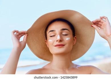 Beautiful Woman Face. Skin Care Concept. Suncream. Suntan Lotion Beautiful Woman Applying on beautiful on Face. Sunscreen Solar Cream. Sun protection.