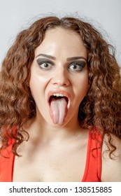 Beautiful woman face with tongue out close-up. Curly hair