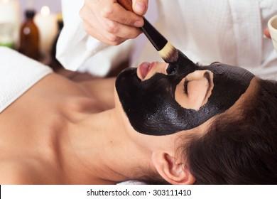 Beautiful woman with facial mask at beauty salon. Spa treatment