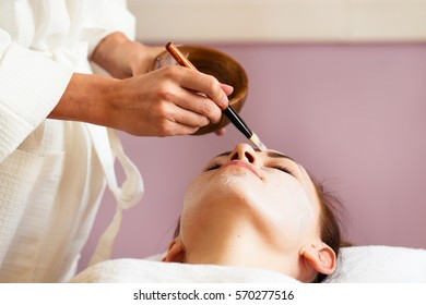 Beautiful woman with facial mask at beauty salon. Spa treatment.