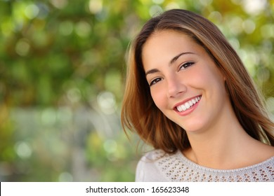 Beautiful woman facial with a perfect white smile outdoor with a green background