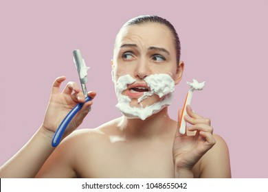 beautiful woman with fake mustache, beard on pink background has shave with razors