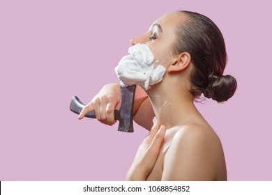 beautiful woman with fake mustache, beard on pink background has shave with hatchet