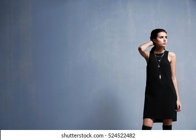 Beautiful woman in fashion clothes on grey background